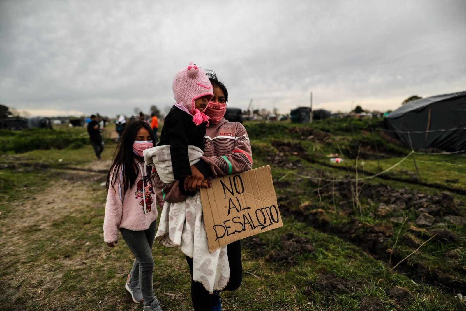 -FOTOGALERÍA: 9 de 23- AME5908. GUERNICA (ARGENTINA), 18/09/2020.- Una mujer camina con sus hijas durante una manfiestación contra el desalojo el 15 de septiembre de 2020, en la toma de tierras de la localidad de Guernica, a 30 km de Buenos Aires (Argentina). Más de mil personas en condición de pobreza se instalaron desde el 20 de julio en un terreno de 100 hectáreas ubicado en Guernica, conformando la más grande toma de tierras en la provincia de Buenos Aires. EFE/ Juan Ignacio Roncoroni